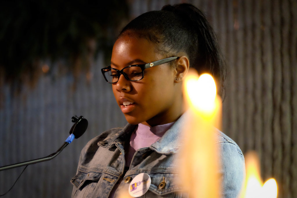 B-PEACE teen organizer Victoria speaking at the vigil, and Emily and Jaylean lighting candles in memory of those killed.